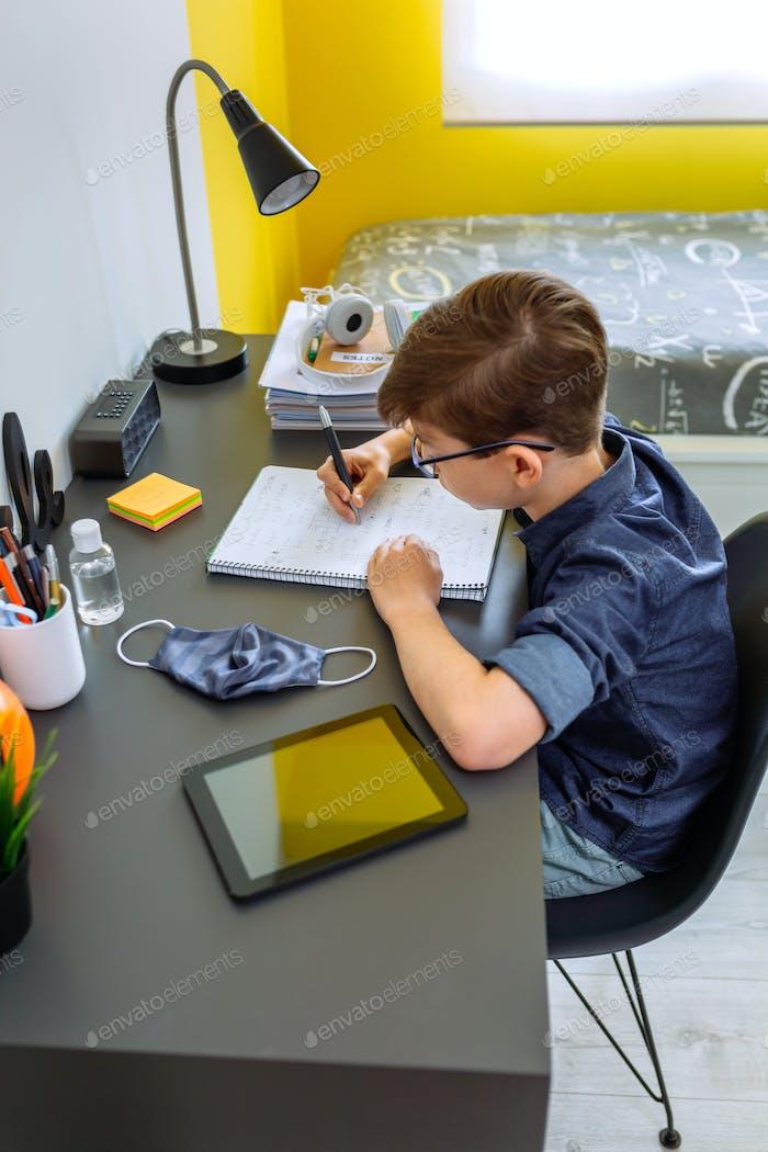 Jugendlicher macht Hausaufgaben in seinem Zimmer