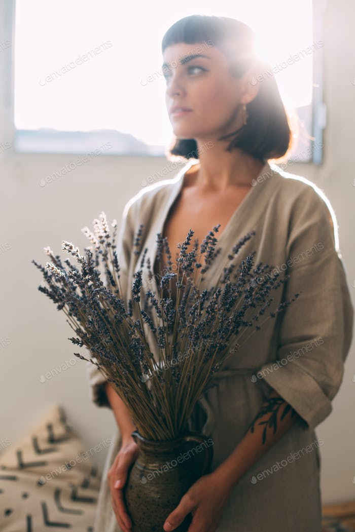 Woman in vintage dress holding lavender in hands