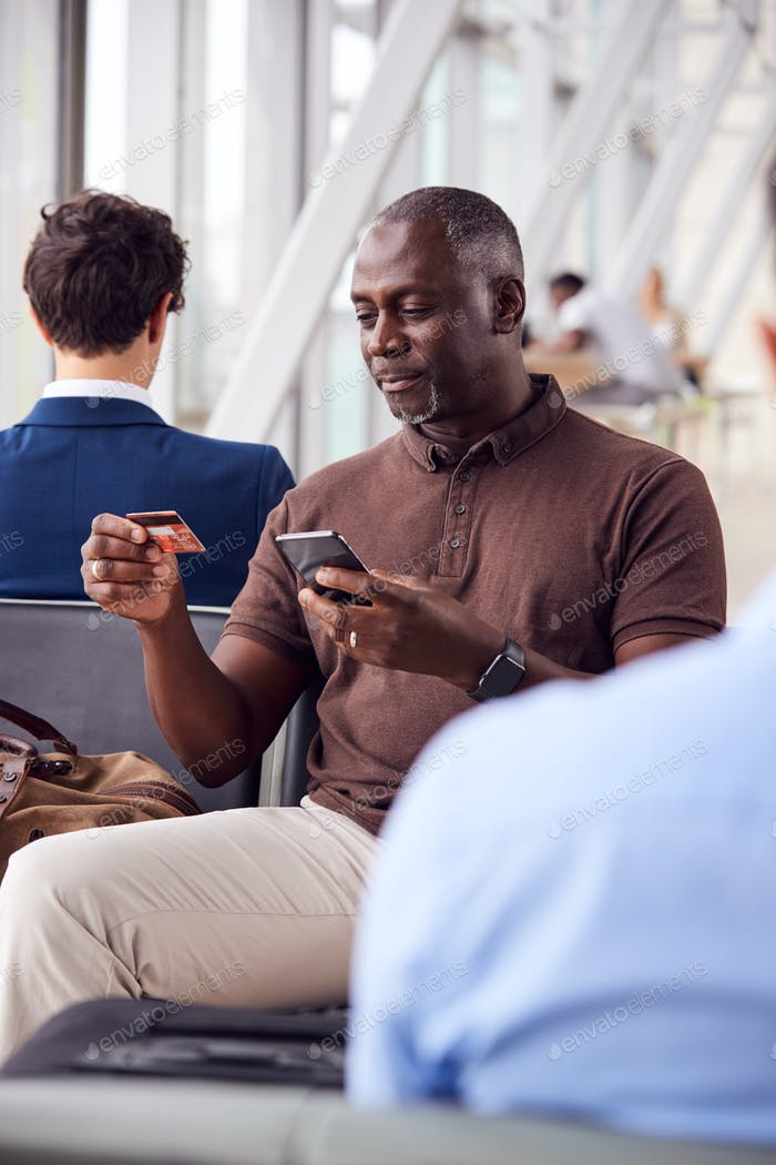 Businessman Sitting In Airport Departure Lounge Shopping Online Using Mobile Phone