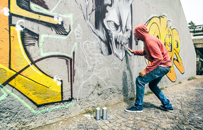 Street artist painting colorful graffiti on generic wall