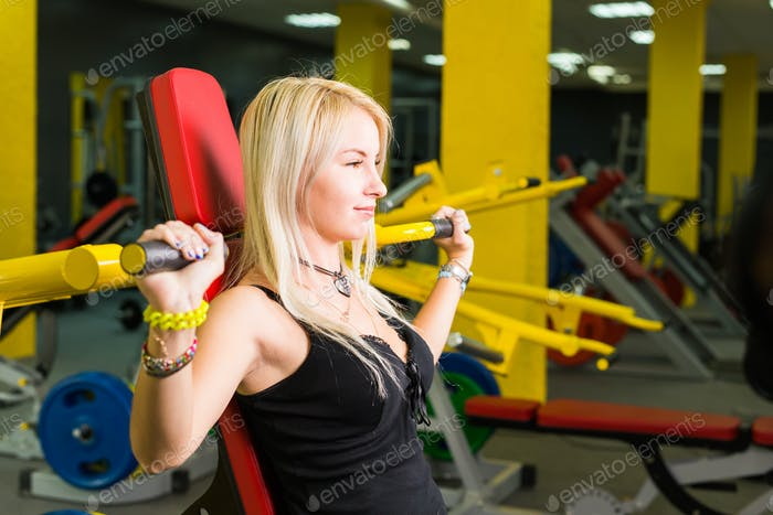 sport, fitness, lifestyle and people concept - Beautiful woman flexing muscles on gym machine