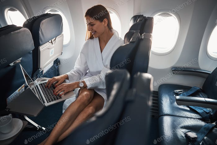 Female in dressing gown using laptop on a plane