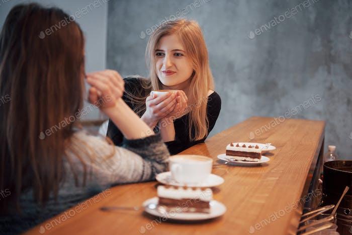 besten Freunde mit Verabredung im Café oder Restaurant. Schöne Mädchen sprechen oder kommunizieren