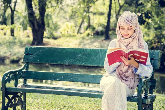 Islamic woman reading the book at the park