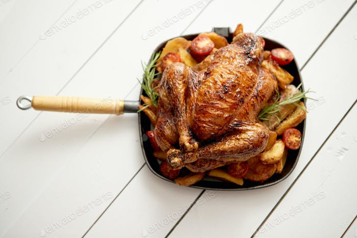 Roasted whole chicken in cast iron black pan