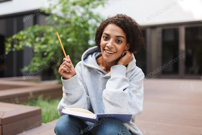 Pretty girl with dark curly hair sitting with open book on knees and happily looking in camera