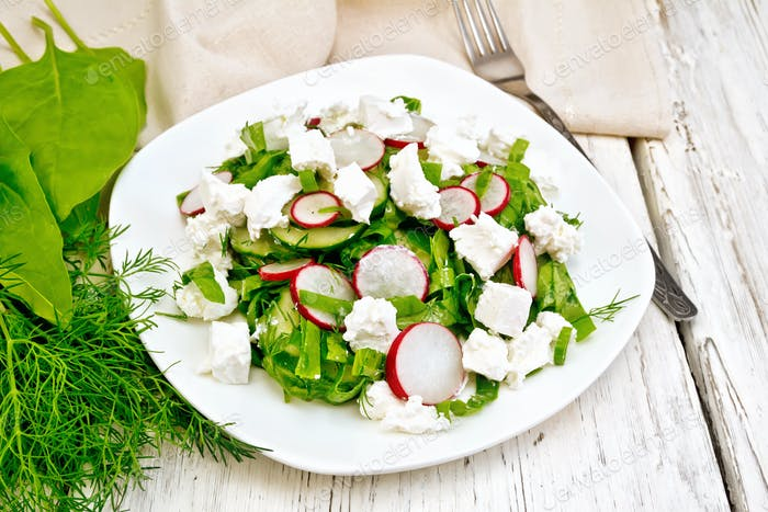 Salad with cheese and radishes in plate on light board