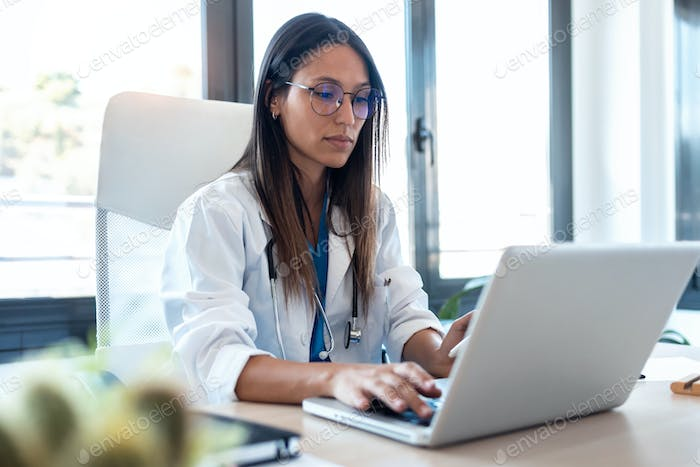 Confident young female doctor using her mobile phone while working on laptop in the consultation.