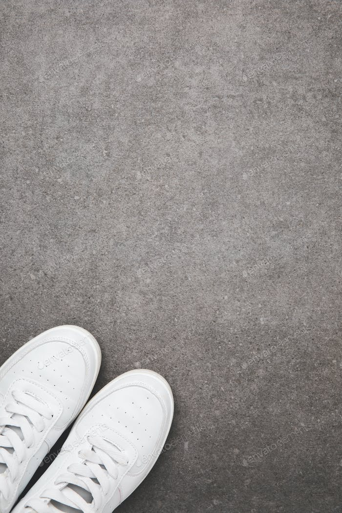 top view of stylish white shoes on concrete surface