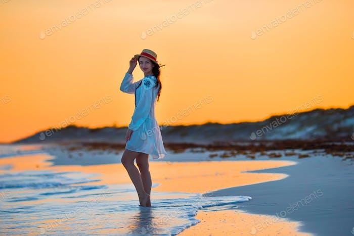 Junge schöne Frau an tropischer Küste in Sonnenuntergang. Glückliches Mädchen im Kleid am Abend auf der