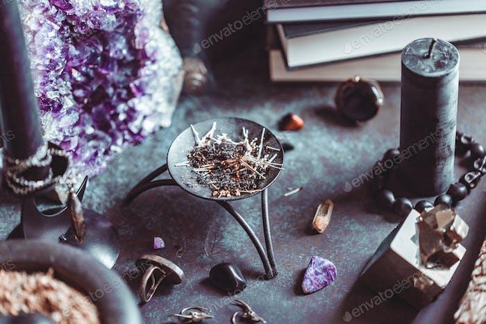 Geräucherte Kräuter auf einem Hexenaltar für ein magisches Ritual zwischen Kristallen und schwarzen Kerzen.