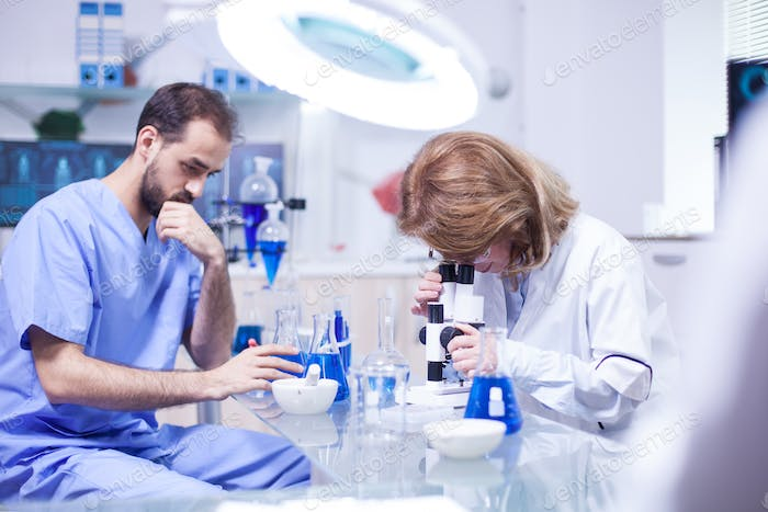 Middle age female scientist working with microscope in laboratory