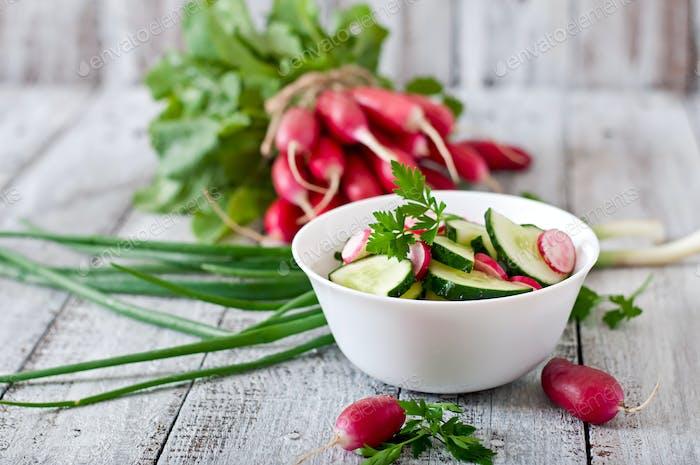 Frischer Salat von Gurken und Radieschen in einer weißen Schüssel auf dem alten hölzernen Hintergrund
