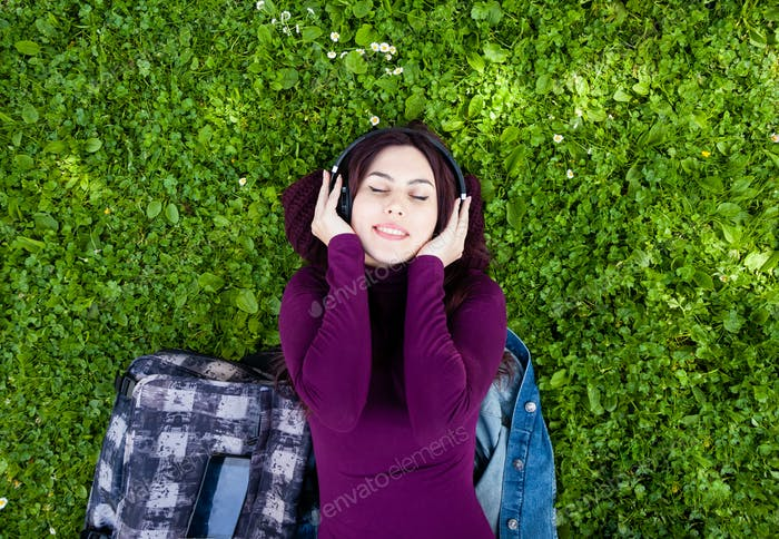 Cute young woman listening music with headphones.