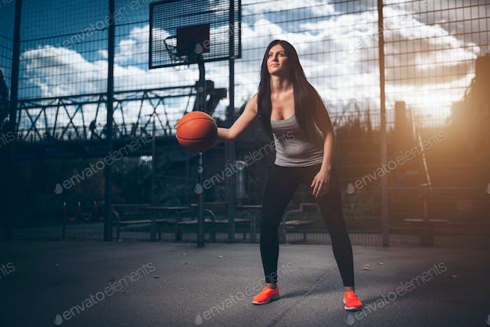 Jugador de baloncesto Mujer entrenando al aire libre en una cancha local