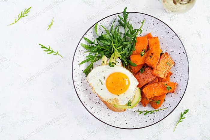 Avocado sandwich with fried egg and fried sliced pumpkin with arugula