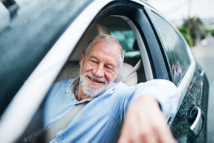 Happy senior man sitting in car in driver seat