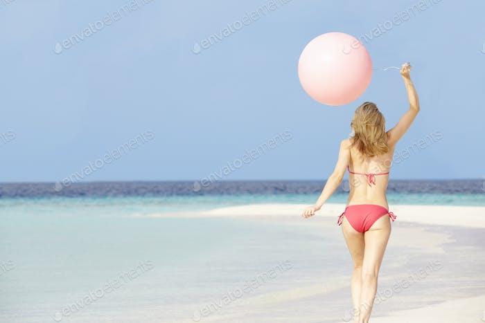 Woman In Bikini Running On Beautiful Beach With Balloon