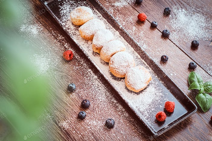 Donuts sprinkled with powdered sugar on a black long plate with raspberry bilberry and mint.