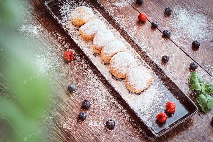 Donuts bestreut mit Puderzucker auf einem schwarzen langen Teller mit Himbeere Heidelbeere und Minze.