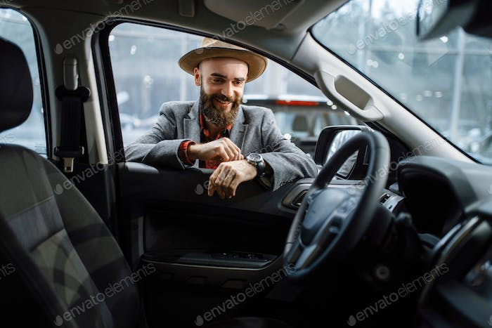 Man in cowboy hat looks on interior of automobile