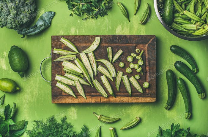 Flay-lay of green vegetables and greens on wooden board