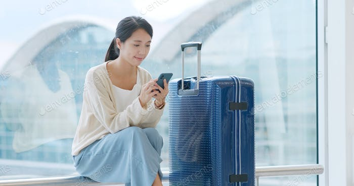 Woman look at the smart phone in the airport