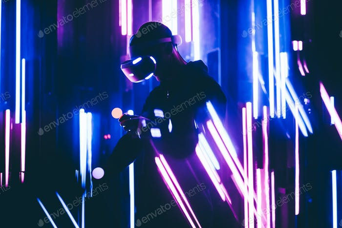Faceless man using VR headset in dark blue interior with neon light lamps