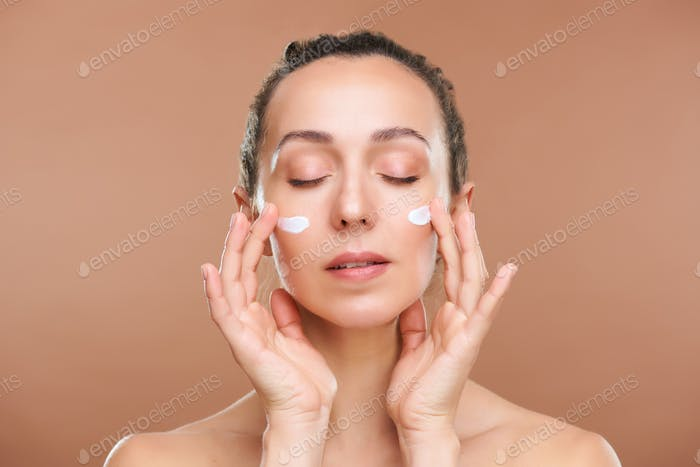 Gorgeous female with closed eyes applying rejuvenating facial cream on cheeks