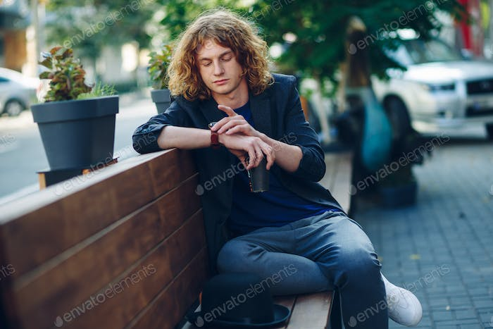 Red haired hipster man sitting on bench looking to his watch