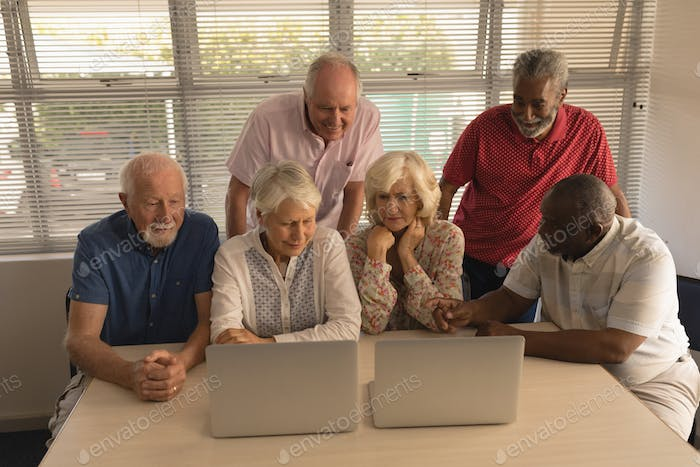 Front view of group of concentrated active senior people using laptop at nursing home