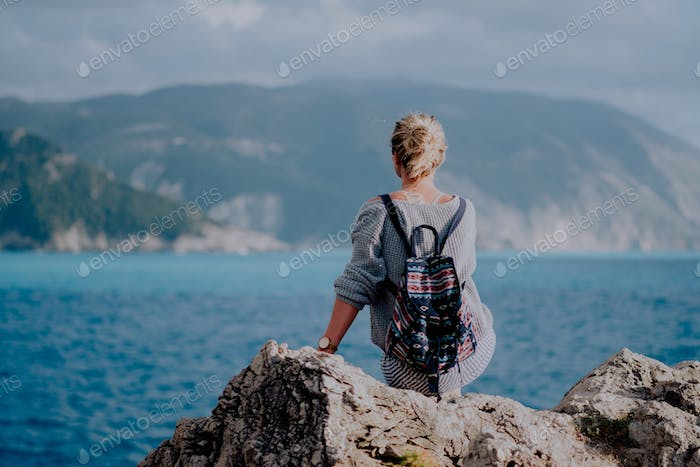 Woman with colorful backpack siting on rocky shore looking to the sea and island on the horizon