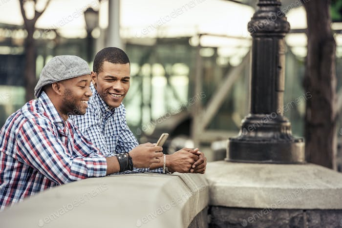 Two men side by side leaning on a parapet by a bridge looking at a smart phone