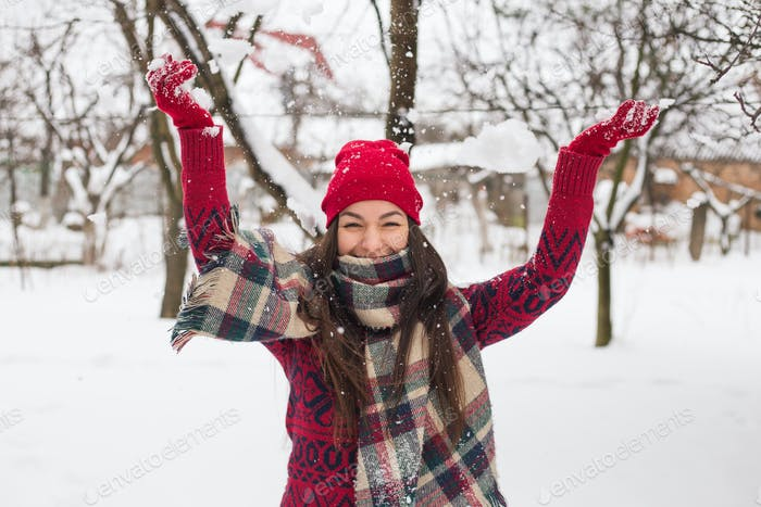 A girl stands against the background of winter and throws snow.