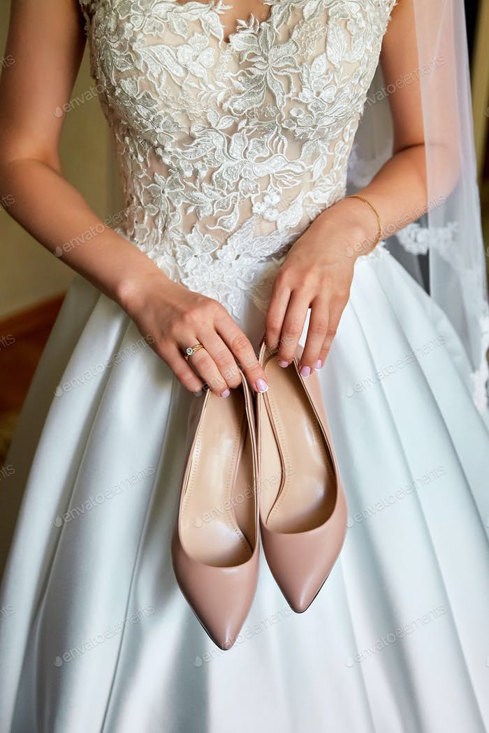 Bride holds the wedding shoes in her hands