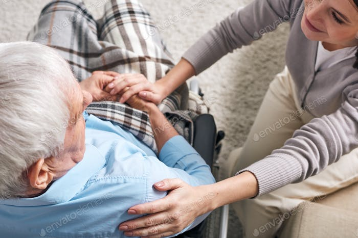 Young supportive female caregiver sitting by senior man in wheelchair