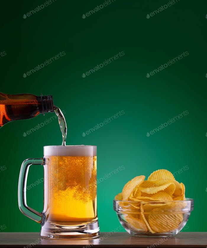 Teller mit Chips und leichtem Bier gießen in Becher auf grünem Hintergrund