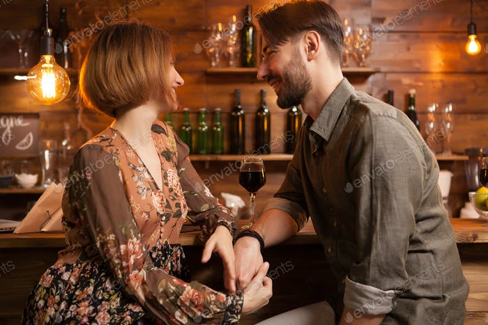 Handsome bearded man looking deeply into his girlfriend eyes and holding her hand