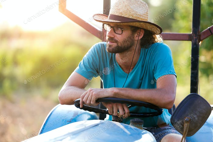 Young hipster farmer in tractor looking for his harvest in the g