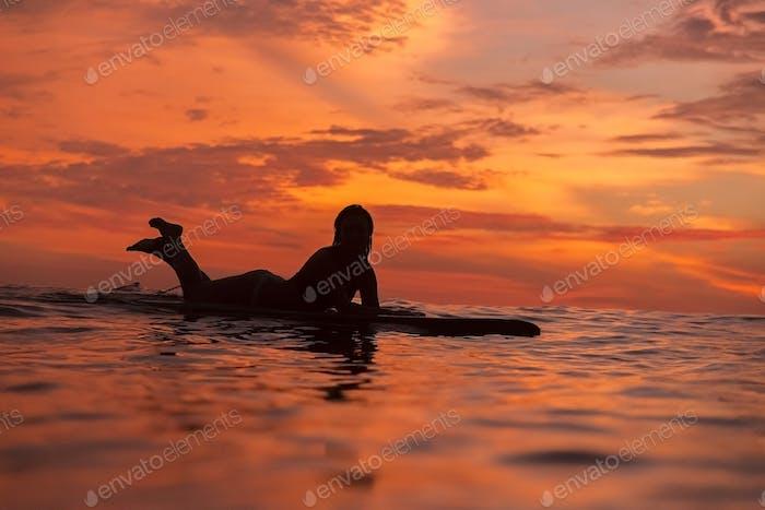 Surfer girl in ocean at sunset time