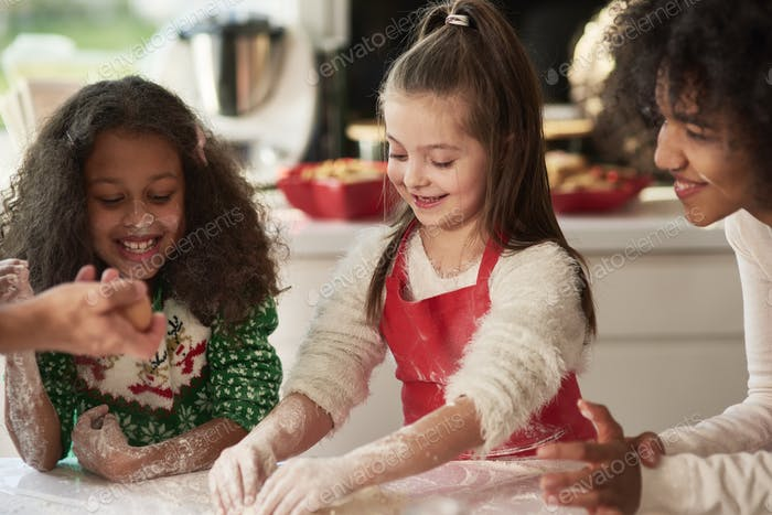 Woman and two girls preparing Christmas cookies