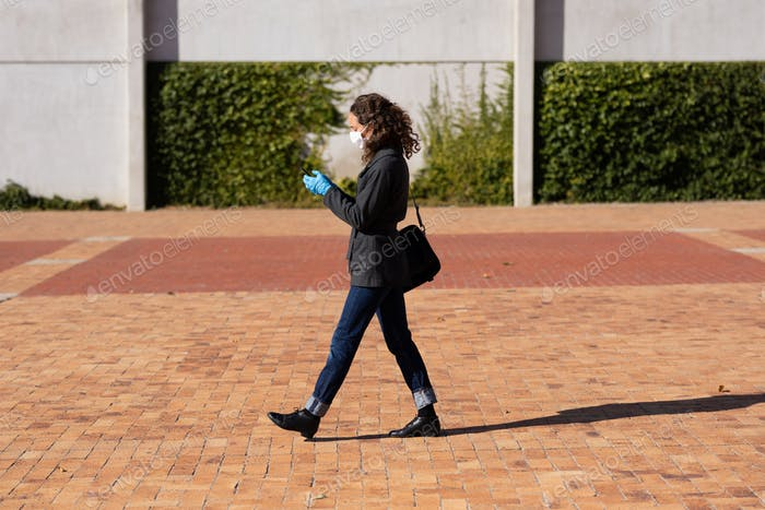 Caucasian woman wearing a protective mask and gloves walking in the streets, using her phone