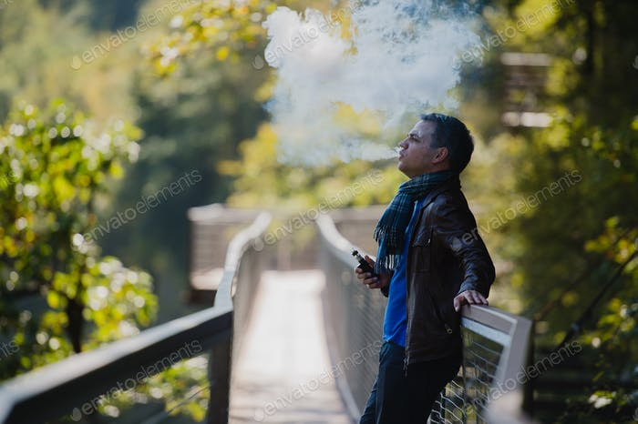 Young man with custom box mode vape device vaping an electronic cigarette outdoor at beautiful place