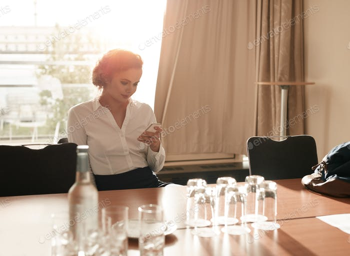 Businesswoman in business conference room using mobile phone