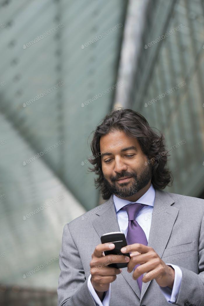 Деловой человек в деловом костюме с полной бородой и вьющимися волосами. Использую его телефон.