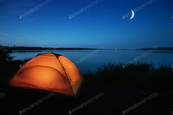 Orange tourist tent lit by a lake