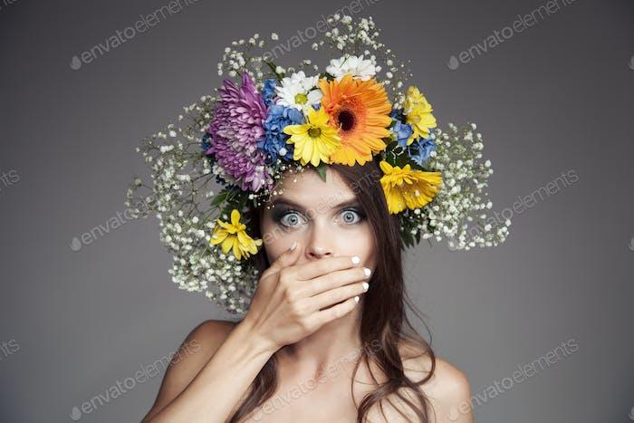Überrascht Frau mit Blumenkranz auf ihrem Kopf.