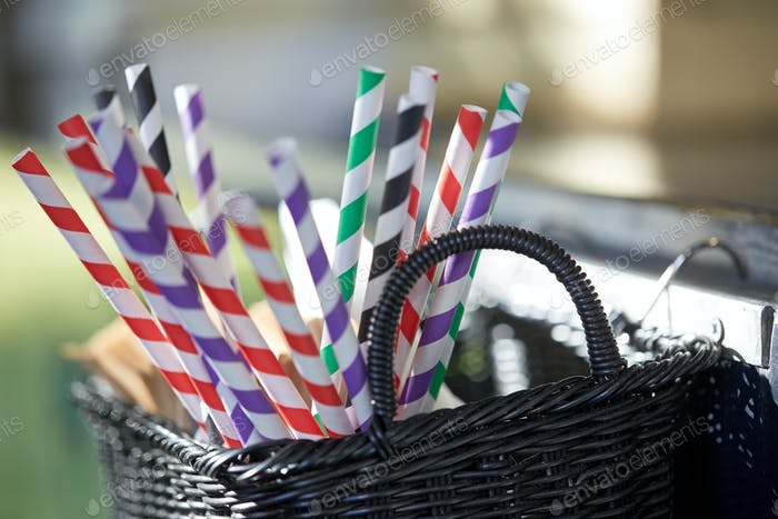 disposable straws in whickered basket outdoors