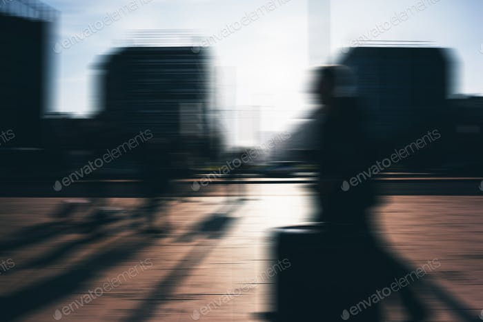 Blurred defocus picture of people walking outdoor on the sidewal