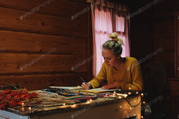 female artist painting a picture with watercolour in a cozy wooden cabin